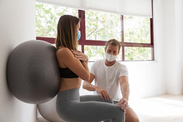 Covid-19 동안 마스크를 착용하는 코치와 피트니스 공 및 필라테스 운동을하는 젊은 여자