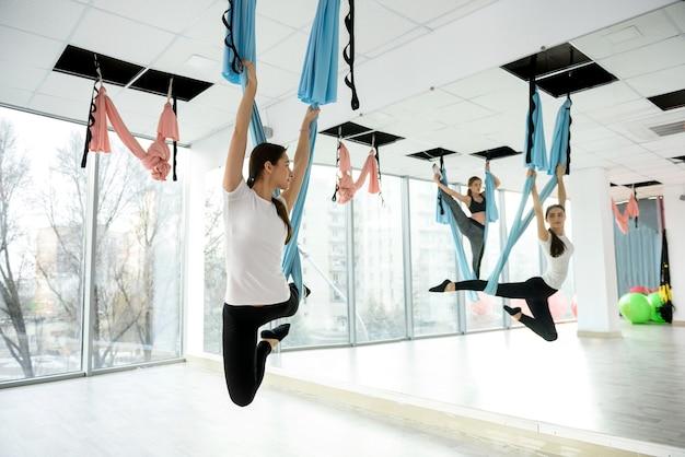 ジムでフライヨガの練習をしている若い女性