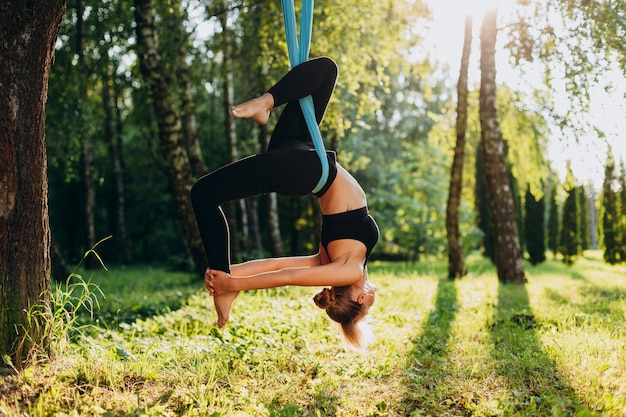 Young woman doing fly yoga at the tree hang upside down.
