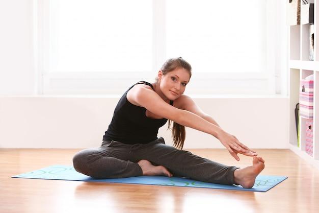 自宅で体操を行う若い女性
