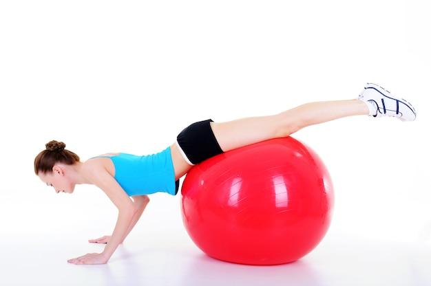 フィットボールで体操を行う若い女性