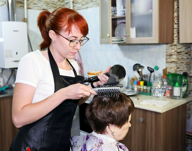 Young woman doing haircut and styling to relatives at home