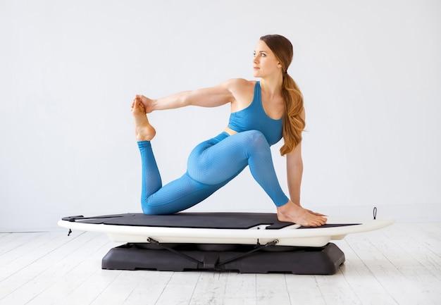 彼女の後肢の筋肉のハムストリングストレッチ運動をしている若い女性