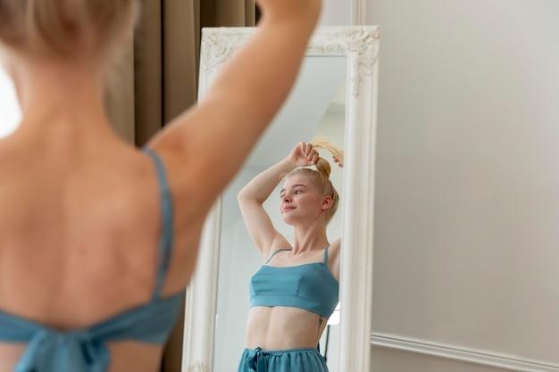 거울에 그녀의 머리를 하 고 젊은 여자