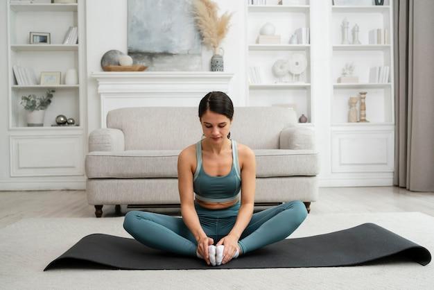 Молодая женщина делает свою тренировку дома на фитнес-коврике