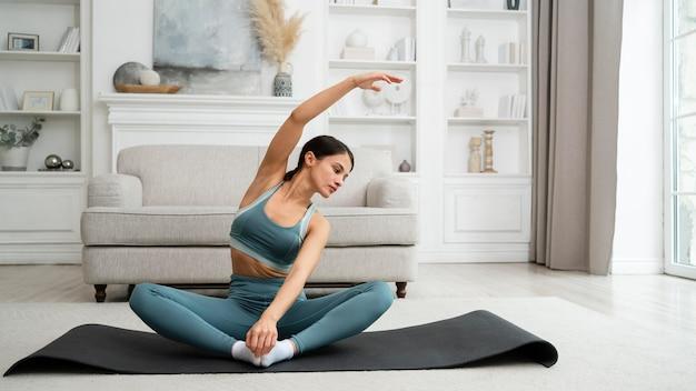 Giovane donna che fa il suo allenamento a casa su un tappetino fitness