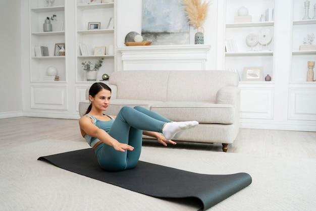 Молодая женщина делает свою тренировку на фитнес-коврике