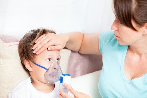 Young woman doing inhalation with a nebulizer son and touches his forehead