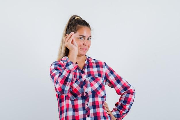 Молодая женщина делает итальянский жест в повседневной рубашке и выглядит весело. передний план.