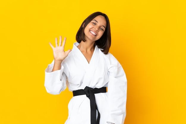 손가락으로 5 세 노란색 배경에 고립 가라테를 하 고 젊은 여자