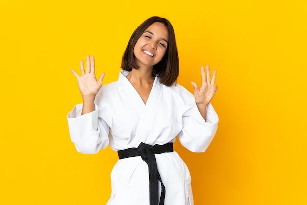 Молодая женщина занимается карате на желтом фоне, считая девять пальцами