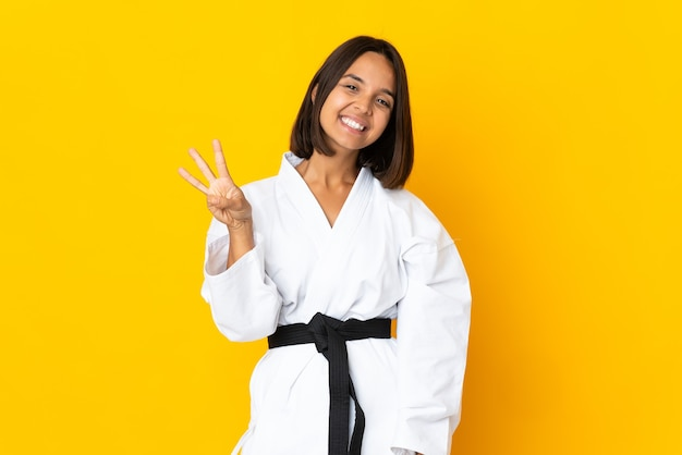 가라테를 하 고 젊은 여자 행복 노란색 배경에 고립 손가락으로 세 세