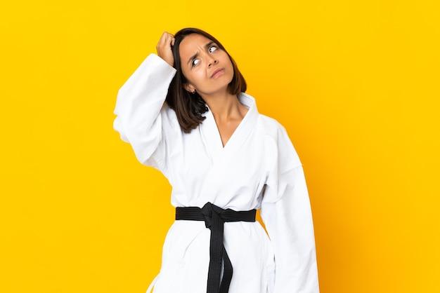 Молодая женщина занимается карате на желтом фоне с сомнениями и смущенным выражением лица