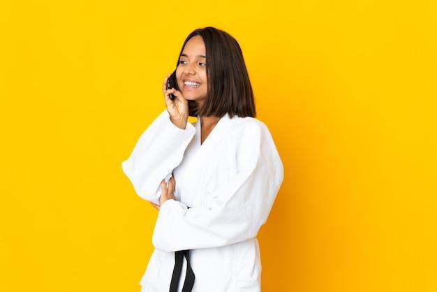 Молодая женщина занимается карате на желтом фоне, разговаривая по мобильному телефону
