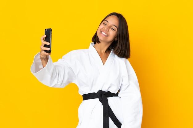 Молодая женщина занимается карате на желтом фоне, делая селфи