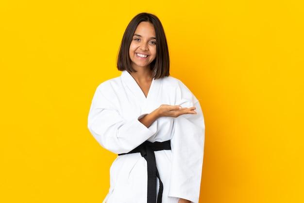 Молодая женщина занимается карате на желтом фоне, представляя идею, улыбаясь в сторону