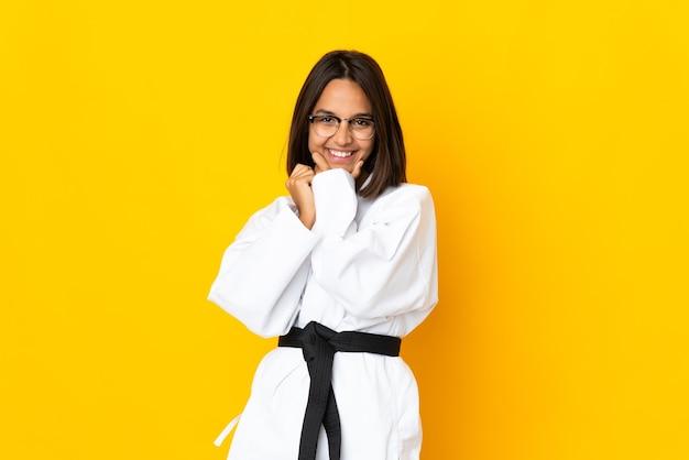 Молодая женщина занимается карате на желтом фоне в очках и улыбается