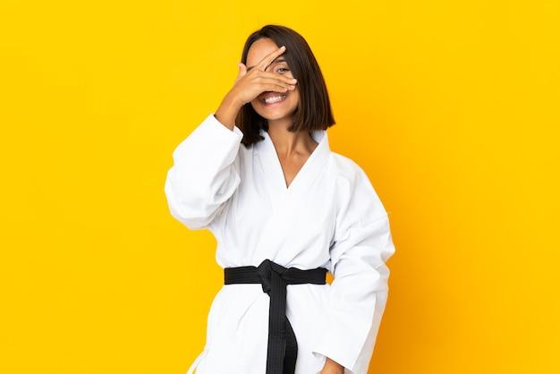 Молодая женщина занимается карате изолированной на желтой поверхности, закрывая глаза руками и улыбаясь