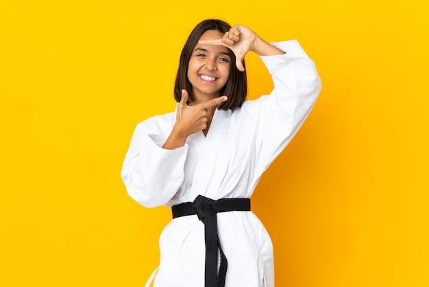 顔に焦点を当てた黄色の壁に孤立した空手をやっている若い女性。フレーミングシンボル