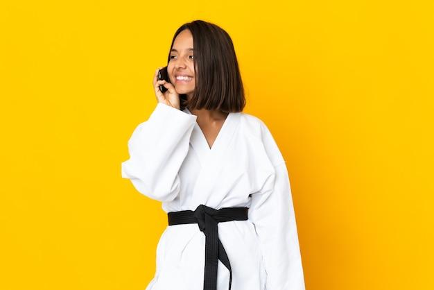 누군가와 휴대 전화로 대화를 유지하는 노란색 벽에 고립 된 가라테를 하 고 젊은 여자