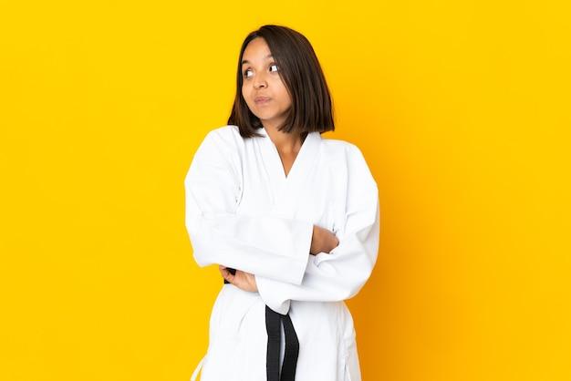 肩を持ち上げながら疑わしいジェスチャーを作る黄色の壁に分離された空手をやっている若い女性
