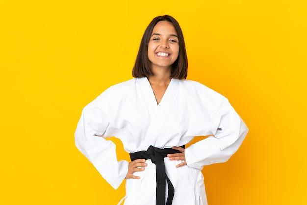 Молодая женщина занимается карате, изолированной на желтой стене, позирует с руками на бедрах и улыбается
