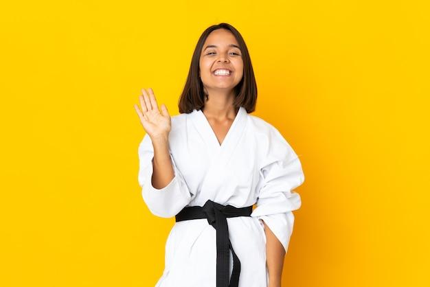 幸せな表情で手で敬礼黄色の壁に孤立した空手をやっている若い女性