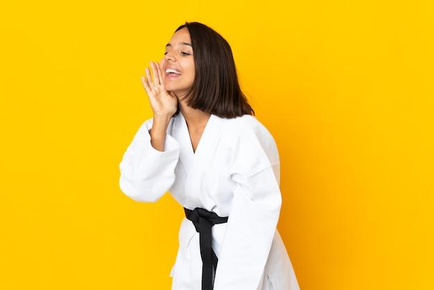 黄色い壁に孤立した空手をやっている若い女性が口を大きく開いて叫んでいる