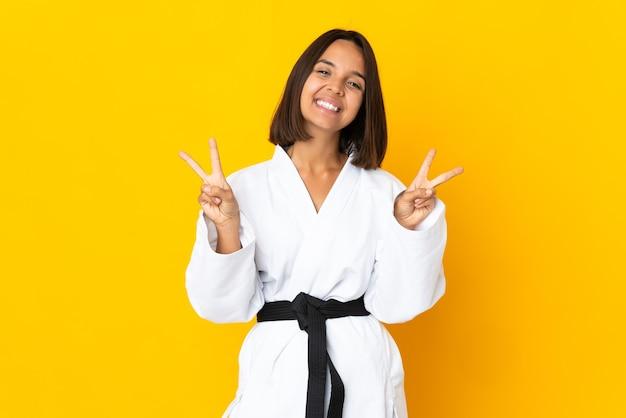 양손으로 승리 기호를 보여주는 노란색 벽에 고립 된 가라테를 하 고 젊은 여자