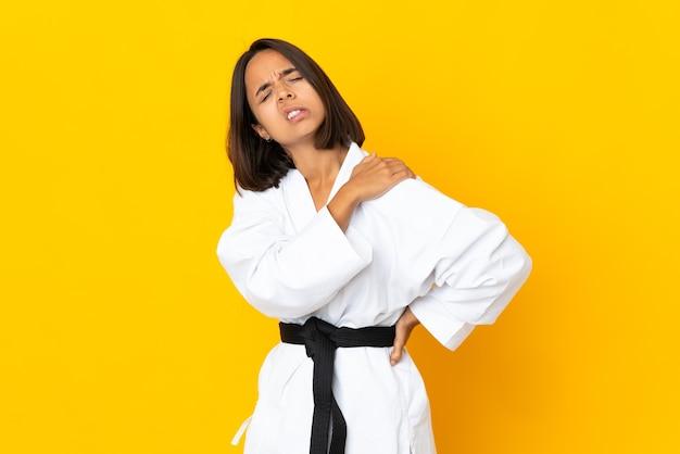 努力したために肩の痛みに苦しんでいる黄色の壁に孤立した空手をやっている若い女性