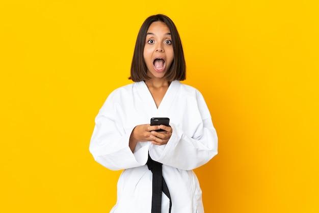 黄色い壁に孤立した空手をやっている若い女性が驚いてメッセージを送信