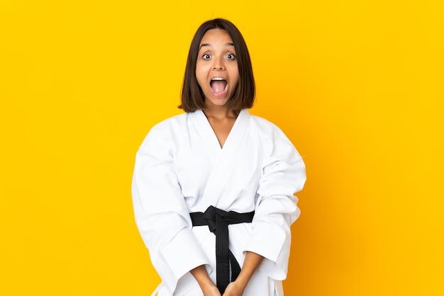 驚きの表情で黄色の壁に分離された空手をやっている若い女性