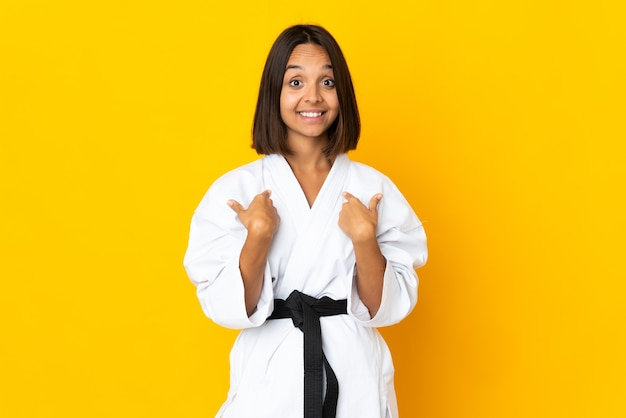 Young woman doing karate isolated on yellow wall with surprise facial expression