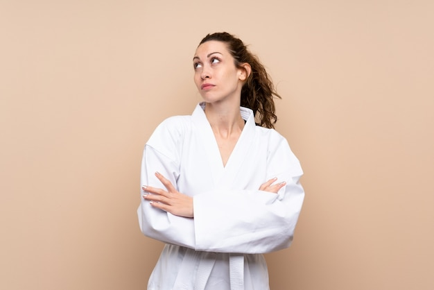 Young woman doing karate making doubts gesture while lifting the shoulders