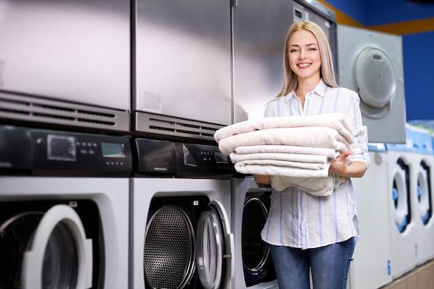 コインランドリーで洗濯をしている若い女性は、カメラの笑顔を見て、手に清潔なタオルを持って、洗濯機の近くに立っています。洗濯、掃除、洗濯、主婦のコンセプト