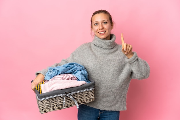 Young woman doing laundry isolated on pink