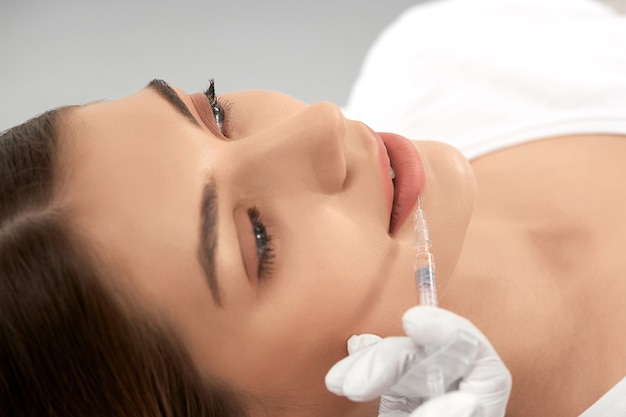 Young woman doing lip augmentation in salon
