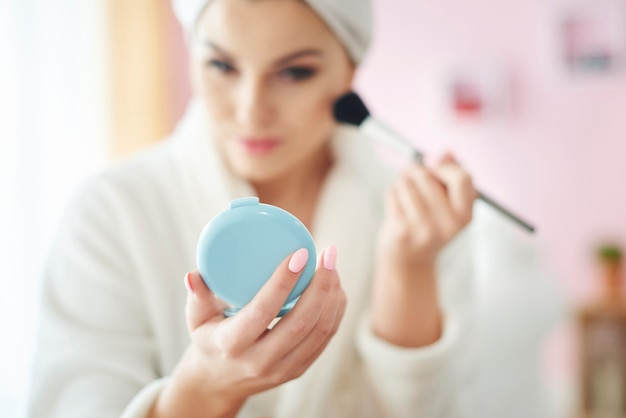 Young woman doing make up at the morning