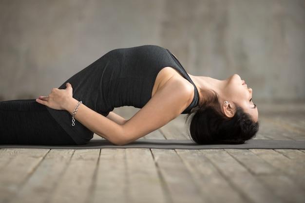 Young woman doing matsyasana exercise, close up
