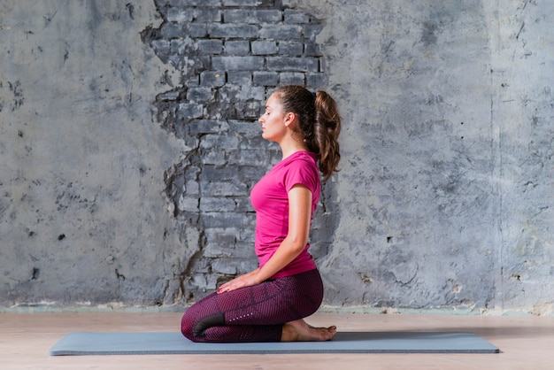 Young woman doing meditating against grey damaged wall