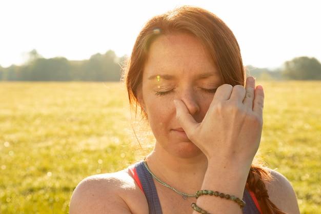 Молодая женщина делает упражнения медитации на открытом воздухе
