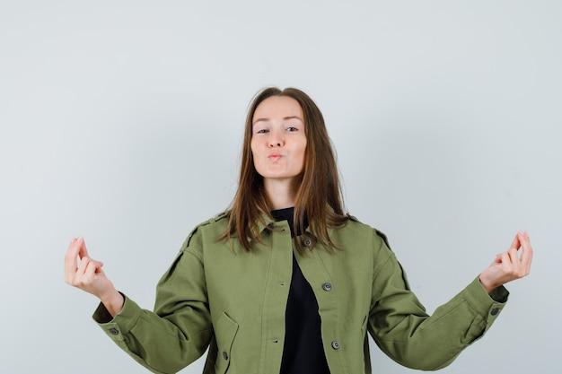 녹색 재킷에 명상을 하 고 진정 찾고 젊은 여자. 전면보기.