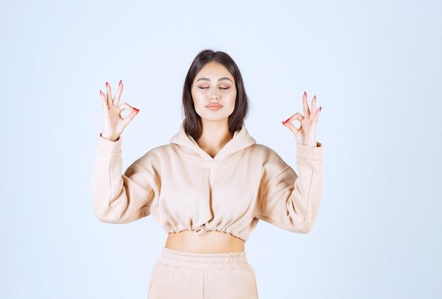 Giovane donna che fa meditazione e che mostra le posture della mano