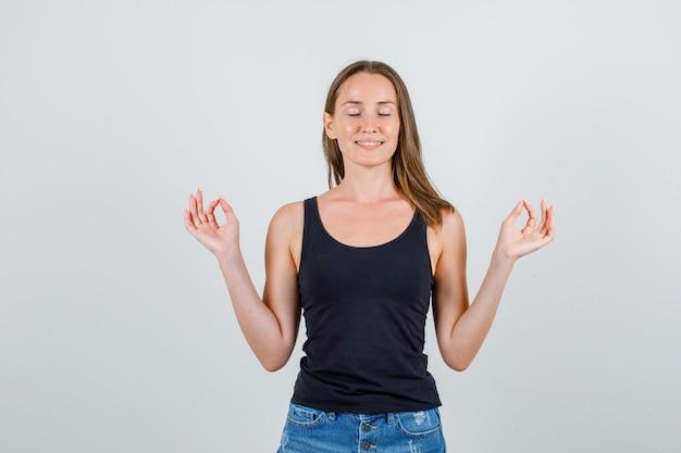 Giovane donna che fa meditazione con gli occhi chiusi in singoletto, pantaloncini e sembra pacifica. vista frontale.