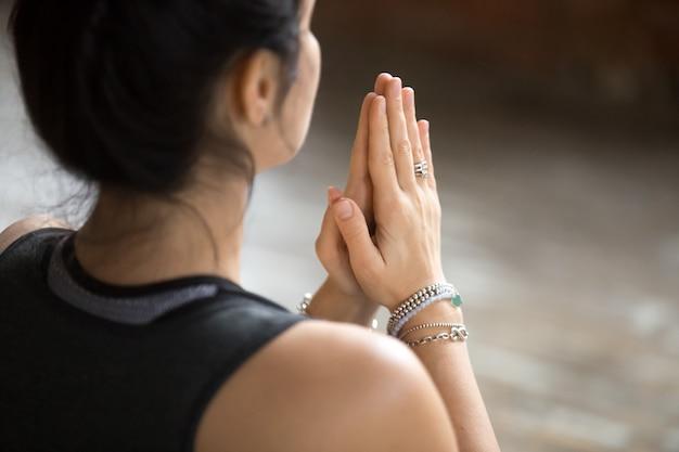 Молодая женщина делает жест намасте, крупным планом