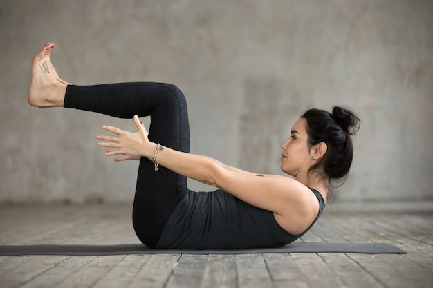 Young woman doing navasana exercise