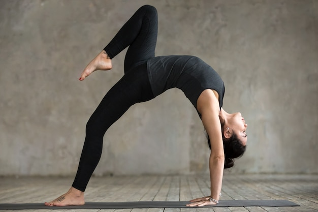 Young woman doing one legged wheel pose exercise
