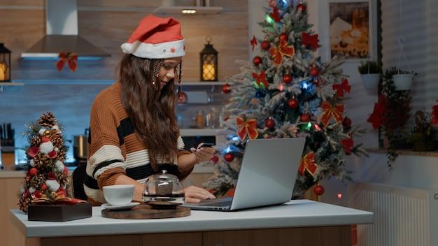 Молодая женщина делает покупки в интернете на ноутбуке