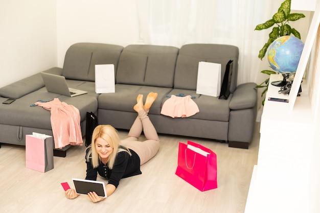 タブレットでオンラインショッピングをしている若い女性