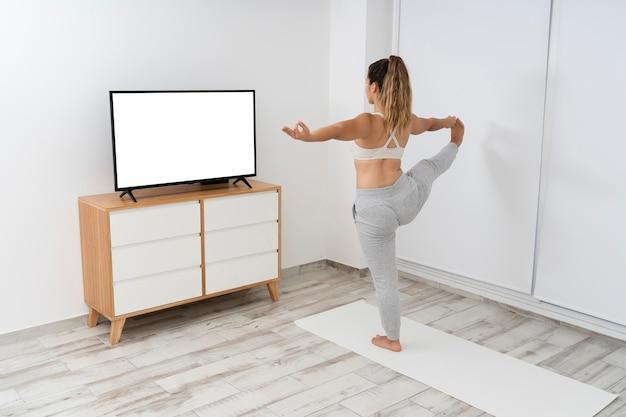 Giovane donna che fa un corso di yoga in linea sulla sua tv